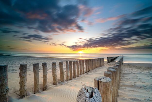 Prise de vue en grand angle d'une terrasse en bois sur le bord de mer menant à la mer au coucher du soleil