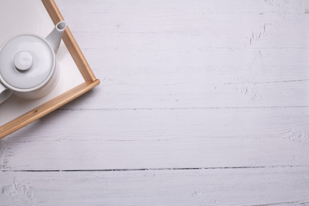 Prise de vue en grand angle d'une théière blanche sur un plateau sur une table en bois blanc