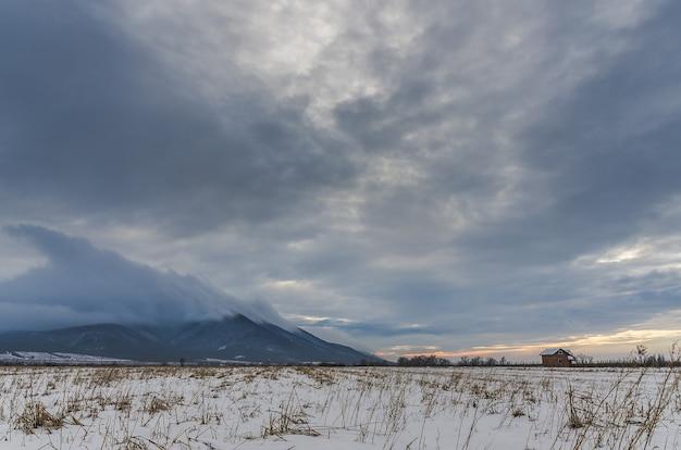 Prise de vue en grand angle d'une vallée couverte de neige sous le ciel nuageux sombre