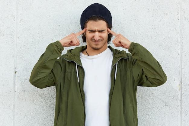 Prise de vue horizontale, un adolescent stressant ferme oui, ressent une pression, maintient les deux index sur les tempes, porte un chapeau noir et un anorak vert