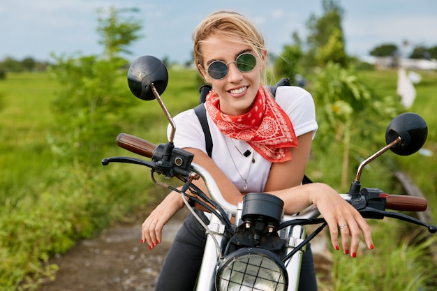 Prise de vue horizontale d'une jolie pilote gaie à la mode porte un bandana sur le cou, porte des lunettes de soleil, s'assoit sur une moto, pose contre la nature verte