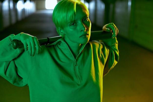 Prise de vue intéressante à la mode dans le parking souterrain aux couleurs néon une fille avec un petit h...