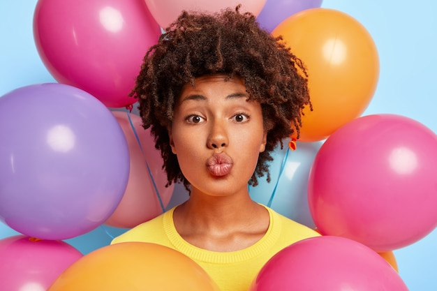 Prise de vue à l'intérieur d'une belle femme à la peau foncée aux cheveux bouclés plie les lèvres, a une beauté naturelle, rencontre des invités pendant son anniversaire, se tient contre des ballons colorés gonflés, vêtue d'un pull jaune