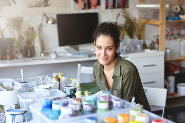 Prise de vue à l'intérieur d'une femme peintre créative avec une belle apparence assise à table entourée d'huiles colorées