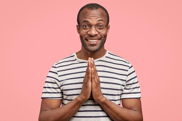 Prise de vue à l'intérieur d'un homme heureux à la peau noire et noire garde les deux mains en signe de prière