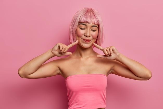 Prise de vue à l'intérieur d'une jeune femme asiatique à l'air agréable ferme les yeux, pointe vers le coin de la bouche, attire votre attention sur son sourire sur le visage, vêtue d'un haut court décontracté, a une coiffure rose à la mode