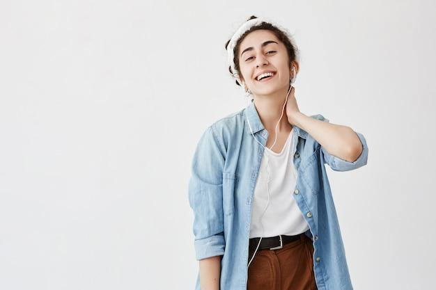 Prise de vue en intérieur d'une jeune femme aux cheveux foncés et ondulés en chignon porte une chemise en jean et un pantalon marron, avec la main sur le cou, utilise un téléphone portable moderne pour se divertir, écoute sa musique préférée avec des écouteurs