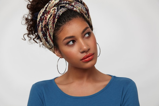 Prise de vue à l'intérieur d'une jeune femme bouclée aux cheveux noirs assez inclinant la tête tout en regardant merveilleusement de côté, vêtue d'un chemisier bleu et d'un bandeau coloré tout en posant sur fond blanc