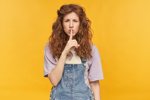 Prise de vue en intérieur d'une jeune femme négative et fatiguée, avec de longs cheveux rouges ondulés, montre un geste de silence avec une expression faciale folle et nerveuse. isolé sur mur jaune