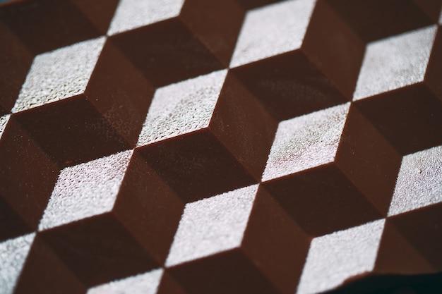 Prise de vue macro d'un carreau de chocolat au lait ou noir avec une ombre.