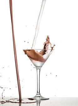 Prise de vue macro avec du chocolat chaud tombant en verre sur blanc en studio