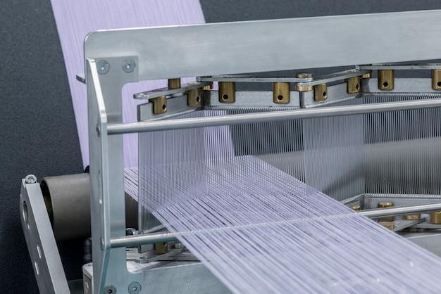 Prise de vue macro du fil de coton se tordant sur l'arbre. machines et équipements dans une usine textile