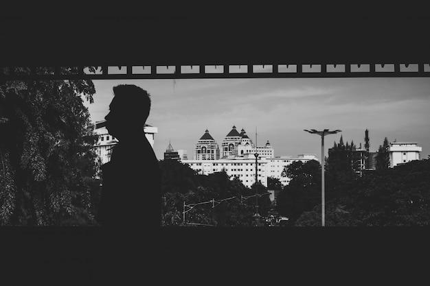 Prise de vue en niveaux de gris d'un homme avec quelques bâtiments