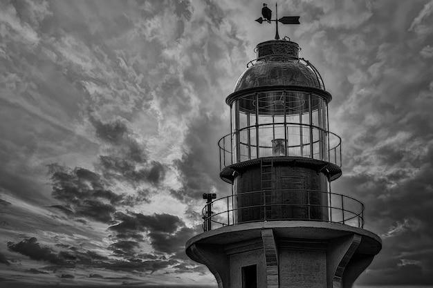 Prise de vue en niveaux de gris d'un phare avec un aigle sur son sommet
