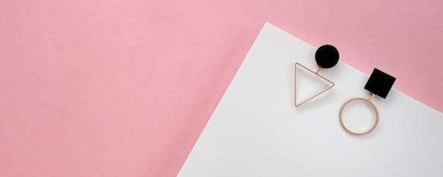 Prise de vue panoramique de boucles d'oreilles modernes géométriques sur fond blanc et rose avec copie espace