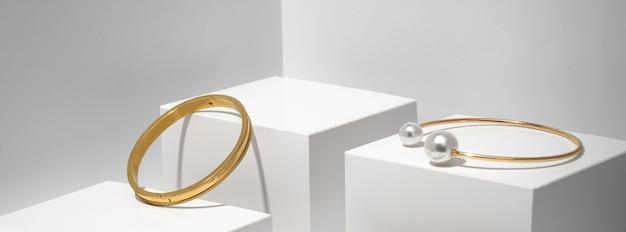Prise de vue panoramique de deux bracelets dorés sur fond géométrique blanc