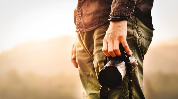 Prise de vue paysage, gros plan du jeune photographe masculin asiatique pendant la tenue de l'appareil photo
