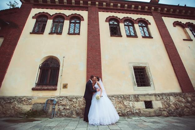 Prise de vue photo de mariage. jeunes mariés marchant dans la ville. couple marié s'embrassant et se regardant. tenant le bouquet. extérieur, plein corps