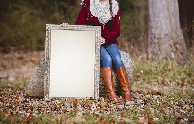 Prise de vue sélective d'une personne tenant un cadre photo vierge