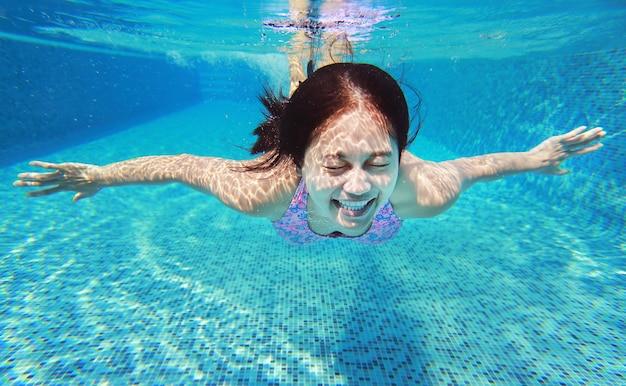 Prise de vue sous-marine de la jeune femme s'amuser en plongée