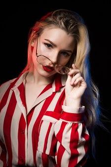 Prise de vue en studio d'une adorable femme blonde à lunettes portant un chemisier rayé, posant avec une lumière rouge et bleue