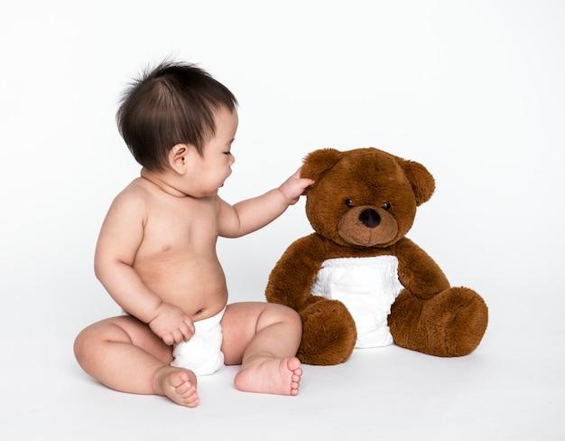 Prise de vue en studio d'un bébé avec un ours en peluche