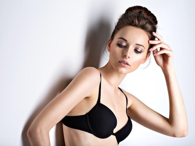 Prise de vue en studio d'une belle et sexy fille aux cheveux longs portant un soutien-gorge noir