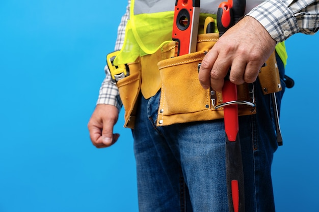 Prise de vue en studio d'un bricoleur inconnu avec les mains sur la taille et la ceinture à outils avec des outils de construction