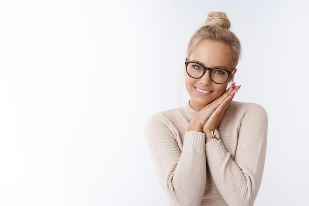 Prise de vue en studio d'une charmante femme blonde caucasienne timide et tendre avec une coiffure en chignon portant des lunettes penchées la tête sur les paumes des épaules pressées et souriante en prenant soin de la caméra, se sentant romantique