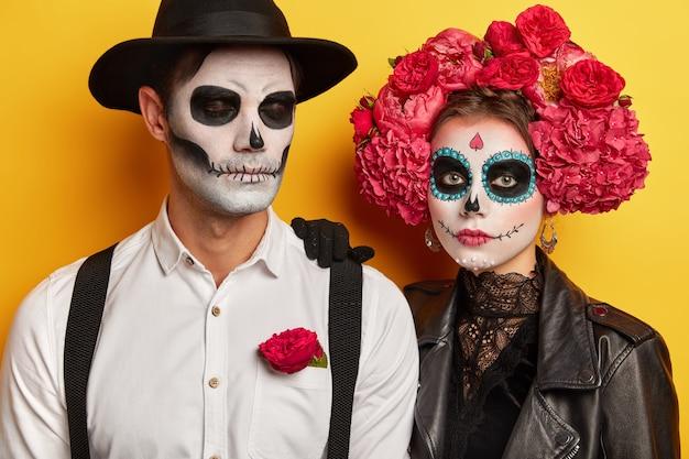 Prise de vue en studio d'un couple sérieux porte un maquillage vif, célèbre les vacances mexicaines traditionnelles, porte une couronne de fleurs, venez à la fête costumée, isolée sur fond jaune. concept du jour de la mort