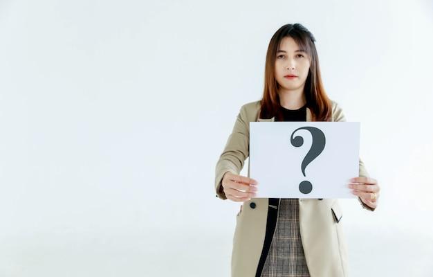 Prise de vue en studio d'une femme officier douteuse en costume d'affaires regarde la caméra tenant un panneau en carton avec un point d'interrogation montrant la curiosité en pensant aux réponses sur fond blanc.