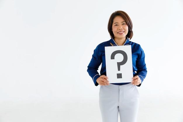 Prise de vue en studio d'une femme officier douteuse en costume d'affaires regarde la caméra tenant un panneau en carton avec un point d'interrogation montrant un sourire pour des réponses sur fond blanc.