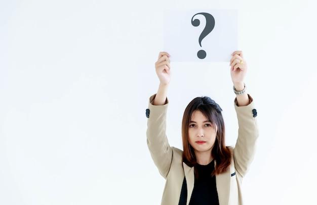 Prise de vue en studio d'une femme officier douteuse en costume d'affaires regarde la caméra tenant un panneau en carton avec un point d'interrogation qui soulève des frais généraux montrant la curiosité en pensant aux réponses sur fond blanc.