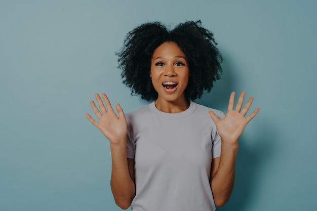 Prise de vue en studio d'une femme à la peau foncée excitée montrant des paumes devant la caméra et faisant preuve d'optimisme, se sentant heureuse et ravie tout en se tenant isolée sur fond bleu. notion de positivité