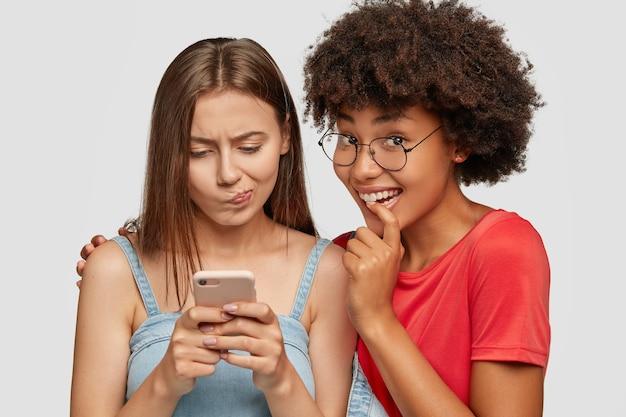 Prise de vue en studio d'une femme de race blanche embarrassée regarde l'écran du téléphone mobile