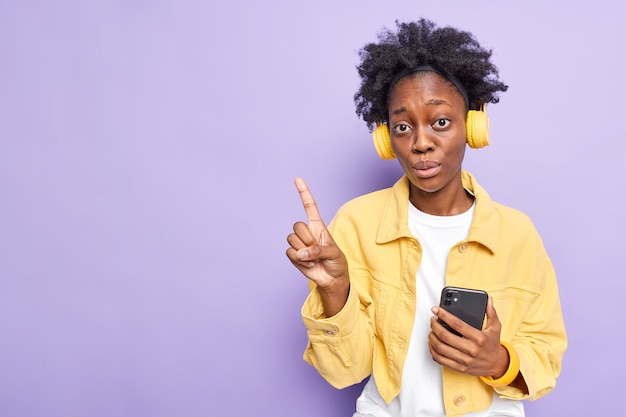 Prise de vue en studio d'une femme surprise avec des cheveux bouclés à la peau foncée dans le coin supérieur gauche utilise un smartphone pour écouter de la musique