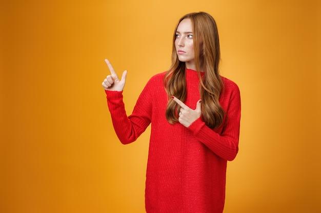 Prise de vue en studio d'une fille rousse suspecte, sérieuse et incertaine, fronçant les sourcils en regardant et en pointant vers le coin supérieur gauche avec un regard strict douteux posant incertain sur fond orange