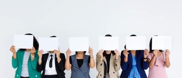Prise de vue en studio d'un groupe sans visage non identifié et méconnaissable d'employées de bureau féminines en affaires portant un support de couverture de signe de papier vide vierge pour le texte publicitaire sur fond blanc.