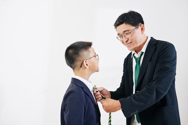 Prise de vue en studio d'un homme asiatique souriant aidant son fils préadolescent à nouer une cravate
