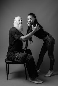Prise de vue en studio d'un homme chauve barbu mature et d'une belle jeune femme asiatique ensemble contre un mur gris en noir et blanc