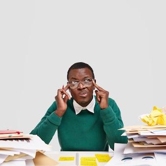 Prise de vue en studio d'un homme perplexe, garde les doigts sur les tempes, rappelle des informations à l'esprit, se concentre sur le processus de travail