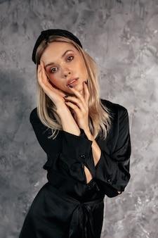 Prise de vue en studio intérieur de belle femme habillée en robe noire posant