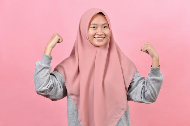 Prise de vue en studio d'une jeune femme musulmane asiatique positive lève les bras montre que les muscles prétendent être des sourires très forts et puissants portent doucement le hijab isolé sur fond rose.