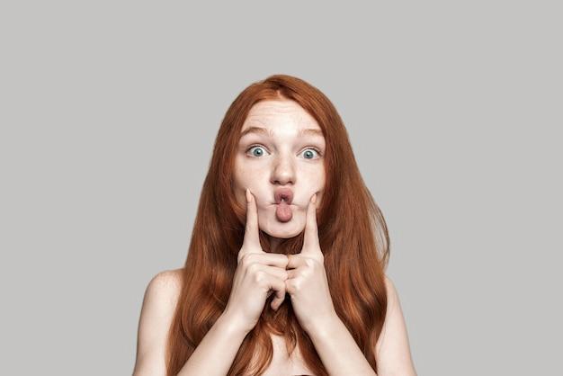 Prise de vue en studio d'une jeune femme rousse heureuse faisant un visage fou et grimaçant en se tenant debout sur fond gris