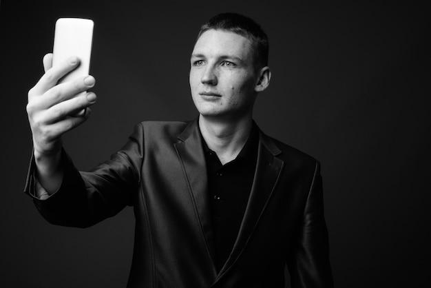 Prise de vue en studio d'un jeune homme d'affaires utilisant un téléphone portable contre un mur gris