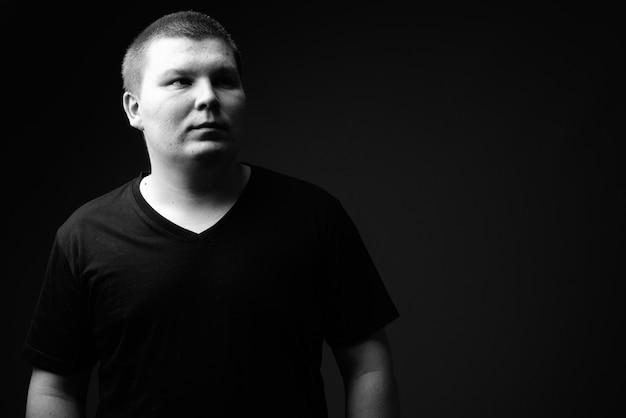 Prise de vue en studio d'un jeune homme en surpoids contre un mur noir en noir et blanc