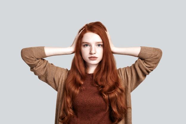 Prise de vue en studio d'une jeune et mignonne adolescente en tenue décontractée touchant ses cheveux rouges et soyeux et regardant la caméra en se tenant debout sur fond gris. portrait de beauté. soin des cheveux.