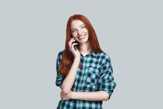 Prise de vue en studio d'une jeune et mignonne femme rousse en tenue décontractée parle au téléphone et sourit en se tenant debout sur fond gris. notion numérique. bannière web