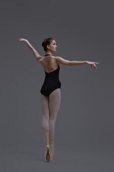 Prise de vue en studio d'une jolie danseuse de ballet portée en tutu dansant sur fond gris.