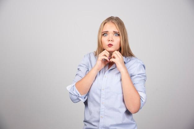 Prise de vue en studio d'une jolie femme tenant la main sous le menton contre un mur gris.